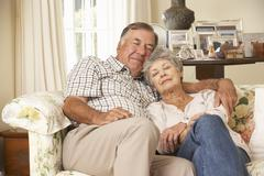 Retired Senior Couple Dozing On Sofa At Home Together - stock photo