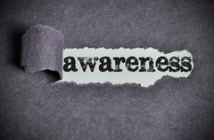 Stock Photo of awareness word under torn black sugar paper