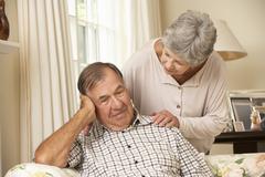 Senior Woman Comforting Unhappy Husband At Home - stock photo