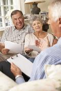 Retired Senior Couple Sitting On Sofa Talking To Financial Advisor - stock photo