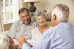 Retired Senior Couple Sitting On Sofa Talking To Financial Advisor Stock Photos