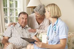 Retired Senior Man Having Health Check With Nurse At Home - stock photo