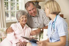 Retired Senior Woman Having Health Check With Nurse At Home - stock photo