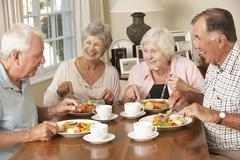 Group Of Senior Couples Enjoying Meal Together Stock Photos