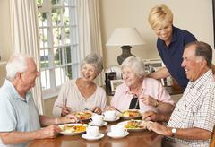 Group Of Senior Couples Enjoying Meal Together In Care Home With Home Help - stock photo
