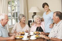 Group Of Senior Couples Enjoying Meal Together In Care Home With Teenage Helper - stock photo