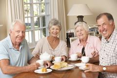 Group Of Senior Couples Enjoying Afternoon Tea Together At Home - stock photo