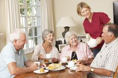 Group Of Senior Couples Enjoying Afternoon Tea Together At Home With Home Help - stock photo