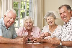 Group Of Senior Couples Enjoying Game Of Cards At Home - stock photo