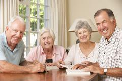 Group Of Senior Couples Attending Book Reading Group Stock Photos