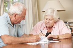Senior Couple Concerned About Debt Going Through Bills Together - stock photo