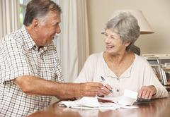 Senior Couple Checking Finances And Going Through Bills Together - stock photo