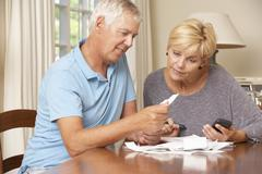 Mature Couple Checking Finances And Going Through Bills Together - stock photo