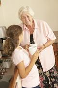 Granddaughter Sharing Cup Of Tea With Grandmother In Kitchen Stock Photos