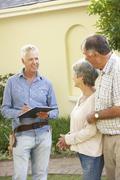 Repairman Giving Senior Couple Estimate For Roof Repair - stock photo