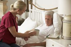 Health Visitor Giving Senior Male Hot Drink In Bed At Home - stock photo
