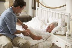 Doctor Taking Pulse Of Senior Male Patient In Bed At Home - stock photo