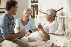 Doctor On Home Visit Discussing Health Of Senior Male Patient With Wife - stock photo
