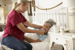 Health Visitor Giving Senior Woman Glass Of Water In Bed At Home - stock photo