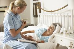 Nurse Taking Pulse Of Senior Patient Patient In Bed At Home Stock Photos
