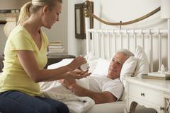 Adult Daughter Giving Senior Male Parent Medication In Bed At Home Stock Photos