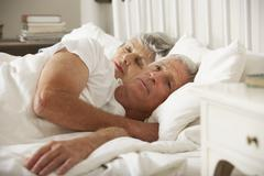 Senior Woman Tries To Be Affectionate Towards Husband In Bed - stock photo