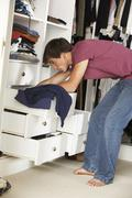 Teenage Boy Choosing Clothes From Wardrobe In Bedroom - stock photo