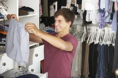 Teenage Boy Choosing Clothes From Wardrobe In Bedroom Stock Photos