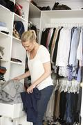 Teenage Girl Choosing Clothes From Wardrobe In Bedroom Stock Photos