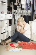 Unhappy Teenage Girl Unable To Find Suitable Outfit In Wardrobe - stock photo