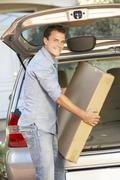 Man Loading Large Package Into Back Of Car Stock Photos