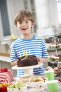 Young Boy Standing By Table Laid With Birthday Party Food - stock photo
