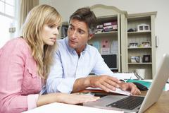 Couple Looking At Finances In Home Office Together - stock photo