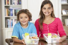 Two Children With Healthy Lunchboxes In Kitchen Stock Photos