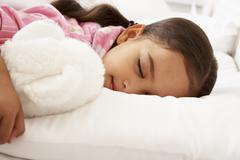Young Girl Asleep In Bed With Cuddly Toy Stock Photos