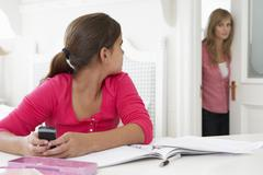 Mother Catches Daughter Using Phone When Meant To Be Studying - stock photo