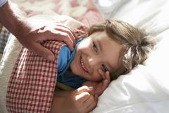 Parent Waking Young Boy Asleep In Bed Stock Photos