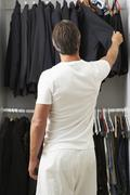 Man Standing In Front Of Wardrobe Choosing Clothes - stock photo