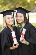 Two Female Students Attending Graduation Ceremony Stock Photos