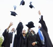 Group Of Students Attending Graduation Ceremony throwing Mortar Boards In The Stock Photos