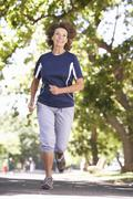 Senior Woman Running Through Park Stock Photos
