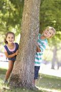 Two Children Hiding Behind Tree In Park Stock Photos