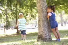 Two Children Playing Hide And Seek In Park - stock photo