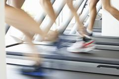 Close Up Of 3 Runners Feet On Running Machine In Gym Stock Photos