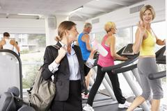 Businesswoman Arriving At Gym After Work - stock photo