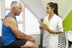 Sports Physiotherapist Treating Male Client Stock Photos