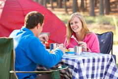 Stock Photo of Couple Enjoying Meal On Camping Holiday