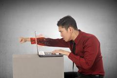 Furious asian business man throws a punch into the laptop Stock Photos