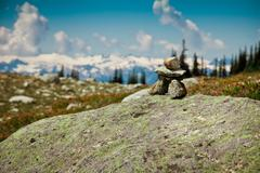 INUKSHUK ROCK FORMATION IN MOUNTAIN SETTING - stock photo