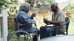 Disabled elderly black woman drinking coffee with husband Stock Footage